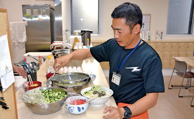 野菜と肉みそを麺に盛りつける小赤澤主査